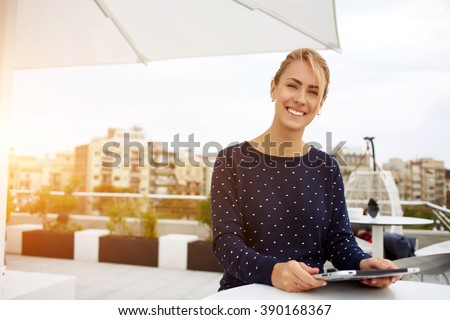 Lovely business woman with smile is sitting with touch pad in comfortable restaurant during recreation time, happy female student works on digital tablet and relaxes in coffee shop after university - stock photo