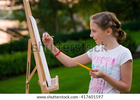 lovely caucasian girl is drawing outdoors to improve her hobby faster. The real lover of the Arts. Young lady draws a picture. - stock photo