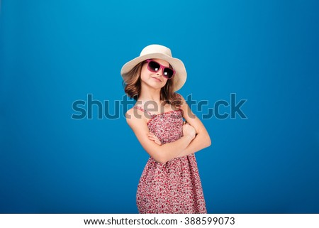 Lovely cheerful little girl in hat and sunglasses standing with arms crossed over blue backgound - stock photo