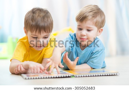 Lovely children brothers reading a book, on the floor at home - stock photo