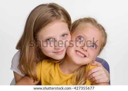 Lovely children in close-up. Two beautiful sisters embrace and look in the camera. The elder girl smiles while the younger makes funny faces. - stock photo