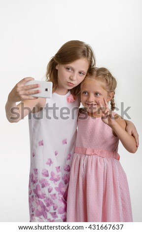 Lovely children take a photo of themselves on the phone. The elder sister made a duckface, while the younger one shows peace gesture. Funny selfie. Isolated. - stock photo