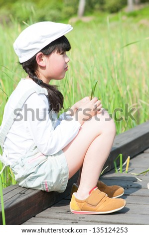lovely Chinese girl playing green grass - stock photo