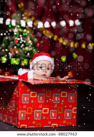 Lovely Christmas toddler sits in large present - stock photo