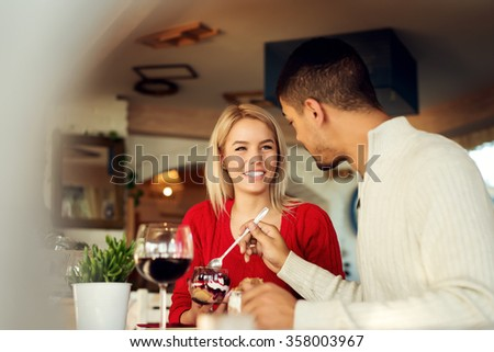 Lovely couple at restaurant enjoy their crucial date, he feeds her with yummy piece of cake. Shallow depth of field. - stock photo