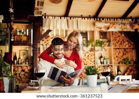 Lovely couple choosing some specialty from menu. While he is sitting she is leaning over his back. Shallow depth of field. - stock photo