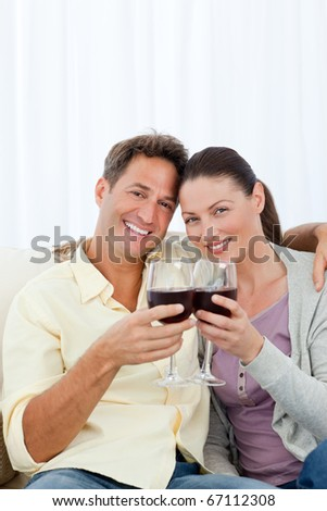 Lovely couple drinking red wine on the sofa at home - stock photo