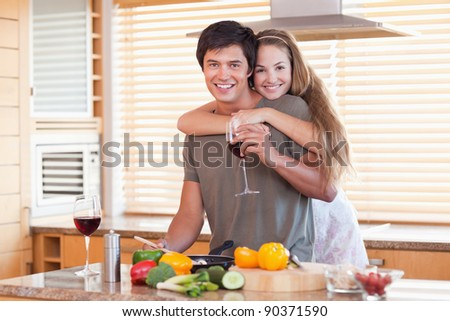 Lovely couple drinking red wine while hugging in their kitchen - stock photo