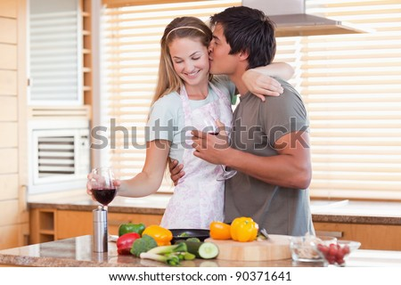 Lovely couple drinking red wine while kissing in their kitchen - stock photo