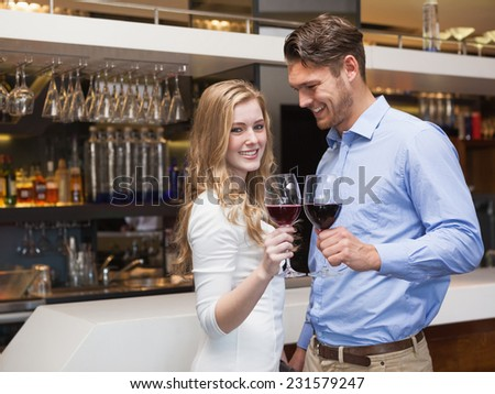 Lovely couple enjoying red wine at the nightclub - stock photo
