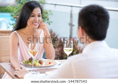 Lovely couple having a romantic time in a restaurant enjoying themselves and the meal - stock photo