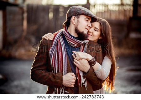 Lovely couple in a stylish brown clothes - backlit  - stock photo