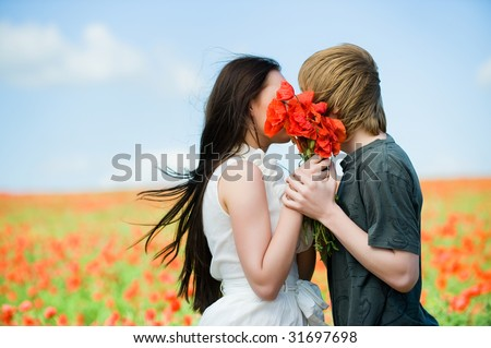 Lovely couple kissing in the poppy field - stock photo