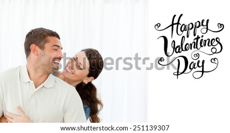 Lovely couple laughing together in the living room against happy valentines day - stock photo