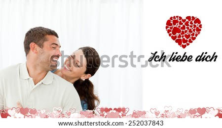Lovely couple laughing together in the living room against ich liebe dich - stock photo