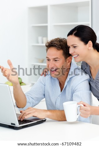 Lovely couple laughing while watching something on the laptop screen in the kitchen - stock photo