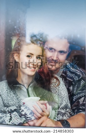 lovely couple sitting indoors (focus on girl's eyes) - stock photo