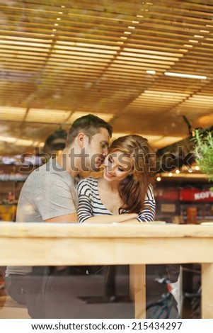 lovely couple sitting indoors in cafe (view through the glass) - stock photo