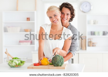 Lovely couple slicing pepper in their kitchen - stock photo