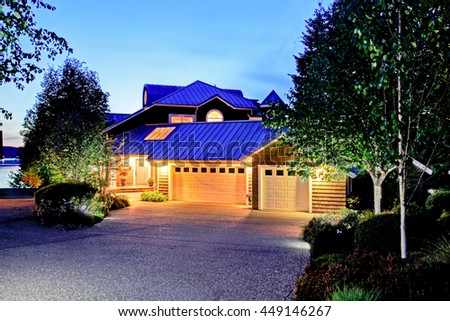 Lovely curb appeal of large luxury house with blue roof. Summer evening. - stock photo