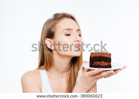 Lovely cute young woman holding piece of chocolate cake and sending a kiss over white background - stock photo