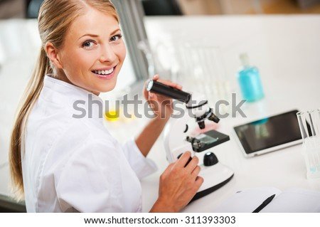 Lovely day in the laboratory. Top view of smiling young female scientist using microscope and looking at camera while working in the laboratory - stock photo