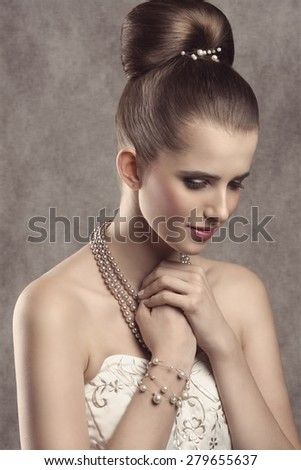 lovely elegant female posing in close-up fashion shoot with fine hairstyle, cute white dress and precious pearls jewellery  - stock photo