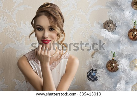 lovely elegant woman posing in romantic christmas portrait with hair-style, make-up and happy expression near decorated xmas tree  - stock photo