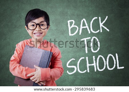 Lovely elementary school student back to school and holding a book in the class while smiling on the camera - stock photo