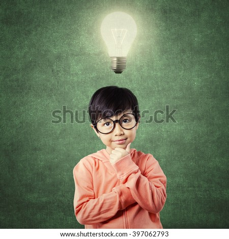 Lovely elementary school student standing in the class with thinking poses while looking up at bright light bulb - stock photo