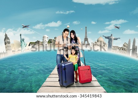 Lovely family carrying bags and use tablet to see and choose the world monument - stock photo