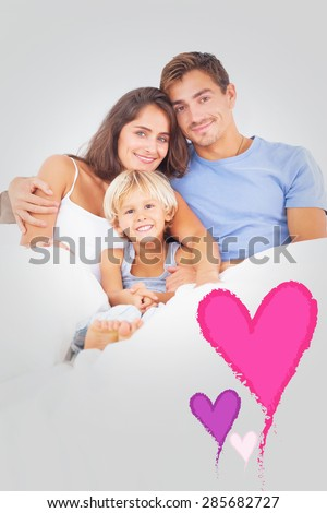 Lovely family embracing against valentines love hearts - stock photo