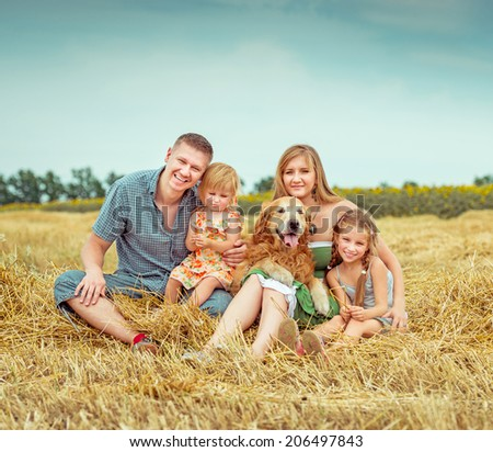 lovely family: parents and two daughters with dog in field - stock photo