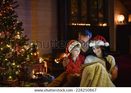 lovely family sharing digital tablet near the wood stove on a winter evening, enjoying the warm Christmas atmosphere in their living room, mother and child wearing a hat of Santa Claus - stock photo