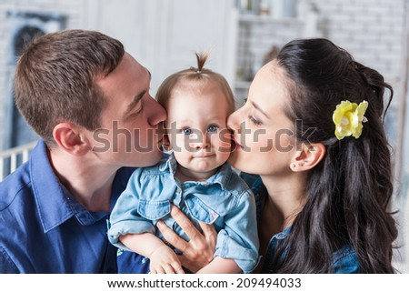Lovely family together at home. Mother and father kissing his year-old daughter - stock photo