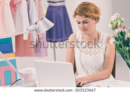 Lovely fashion designer working on the laptop in her studio - stock photo