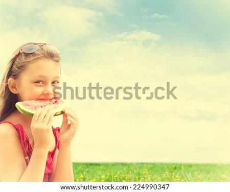 lovely girl eating watermelon on blue sky background - stock photo