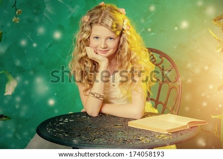 Lovely girl in a lush white dress reading fairy tales under a floral arch over green background.  - stock photo