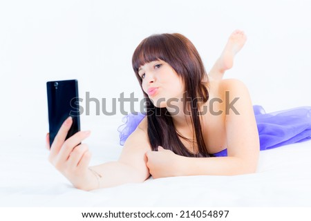 Lovely girl in a purple cocktail dress lying and doing a self-portrait - stock photo
