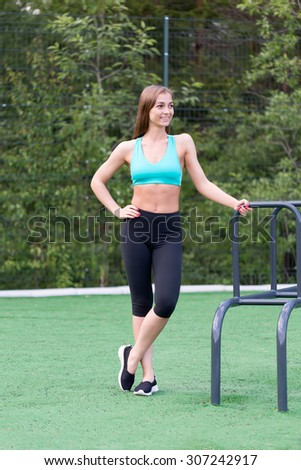 Lovely girl in sportswear standing and smiling on the playground. - stock photo
