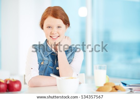 Lovely girl looking at camera with some snack near by - stock photo