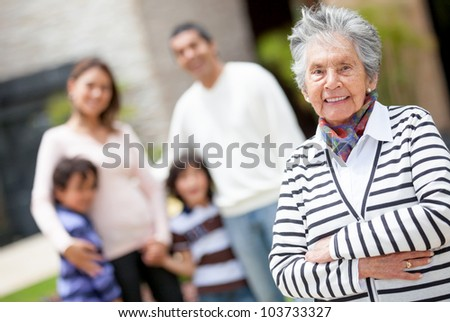 Lovely grandmother smiling with her family at the background - stock photo