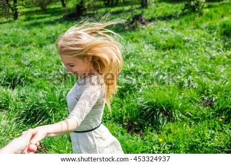 Lovely happy blonde with flying hair holding my hand and dancing around in blossom garden. Point of view - stock photo