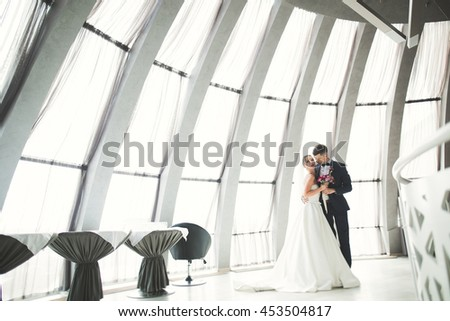 Lovely happy wedding couple, bride with long white dress posing in beautiful city - stock photo