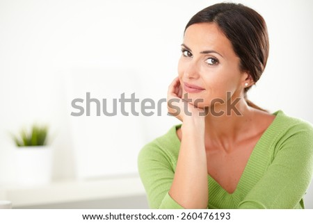 Lovely hispanic female with natural beauty looking elegant and smiling at indoor - copyspace - stock photo