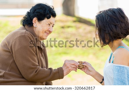 Lovely hispanic grandmother and granddaughter enjoying quality time outdoors sharing snacks. - stock photo