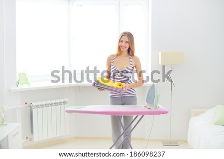 lovely housewife with clothes on light background - stock photo