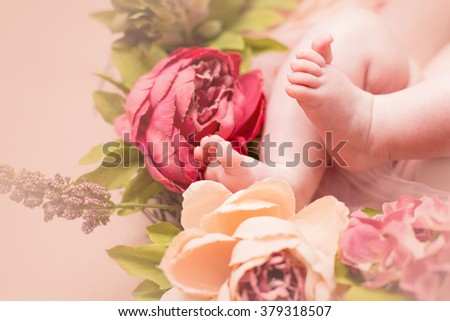 Lovely infant foot with flowers. Newborn baby - stock photo