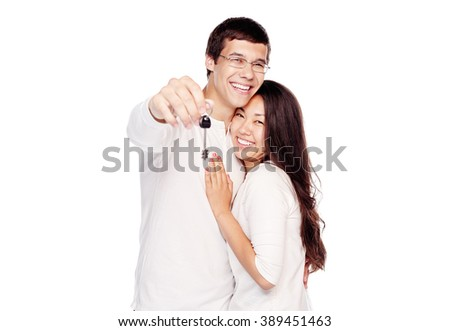Lovely interracial couple, hispanic man and asian girl, showing key of their new house, hugging and smiling isolated on white background - real estate for young family concept - stock photo