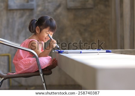 lovely kid practice for writing on white broad before class learning in pre kindergarten - stock photo